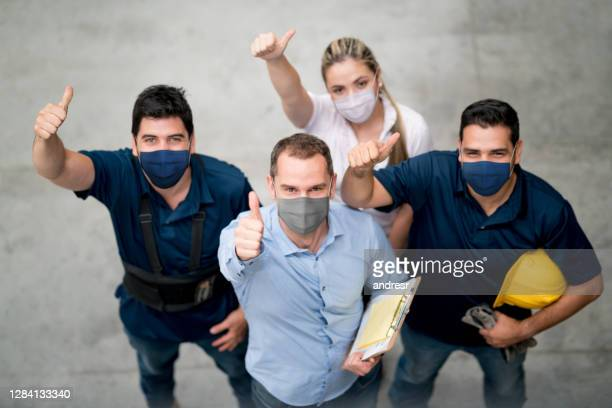 group of workers at a warehouse wearing facemasks and showing their with thumbs up - biosecurity stock pictures, royalty-free photos & images