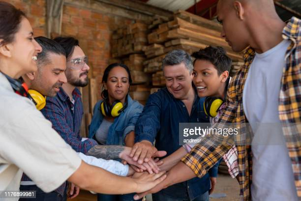 group of workers at a wood factory putting their hands together - trade union stock pictures, royalty-free photos & images