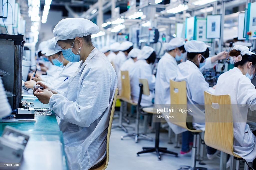 Group Of Workers At Small Parts Manufacturing Factory In