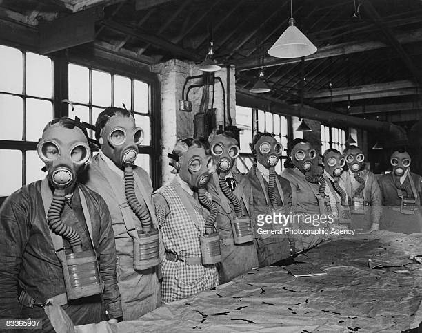 A group of workers at the Seibe Gorman factory in London modelling the company's gas masks which are being produced in preparation for gas attacks...