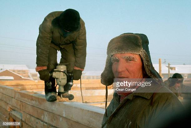 A group of workers build a home of wooden timbers on a very cold day with a temperature of minus 40 degrees Siberia | Location Khanty Mansiysk Russia...
