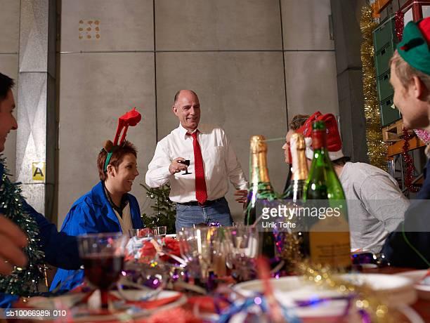 Groupe de travailleurs en hommage au charismas table dans un entrepôt