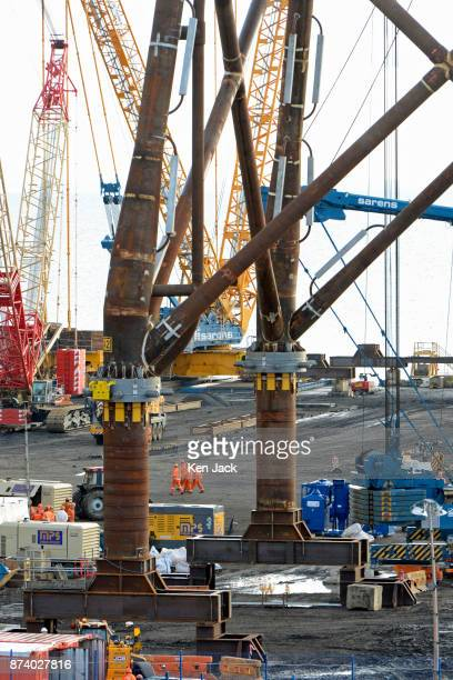 A group of workers is dwarfed by one of the giant steel structures for offshore wind power developments which dominate the Methil yard of engineering...