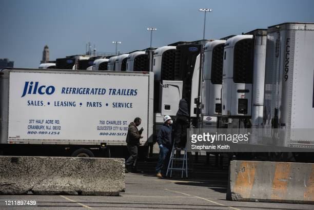 Group of workers make adjustments on a refrigerated truck on the 39th St. Pier on May 5, 2020 in the Brooklyn borough in New York City. New York...