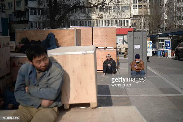 A group of workers rest outside a securities company in Beijing on January 14 2016 China logged its worst economic performance since the global...