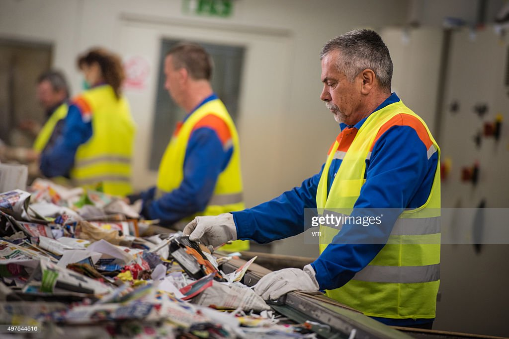 Group of workers sorting papers at recycling plant : Stock Photo