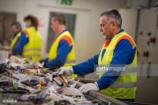 group of workers sorting papers at recycling plant - recycling stock pictures, royalty-free photos & images