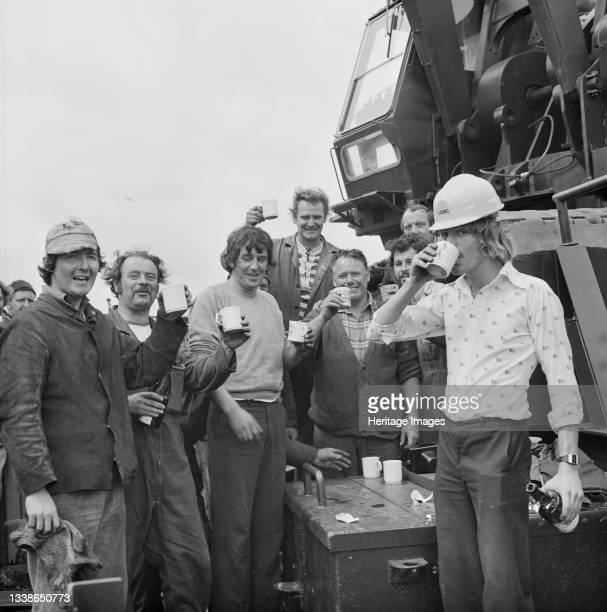 Group of workers toasting the launch of a twin barge from Woolston, Hampshire, for use in the construction of the Peel Common Sewage Works outfall at...