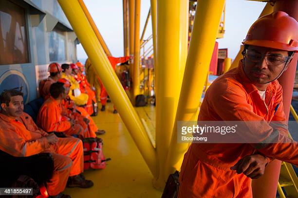 A group of workers wait in the heliport area at the Petroleos Mexicanos PolA Platform complex located on the continental shelf in the Gulf of Mexico...
