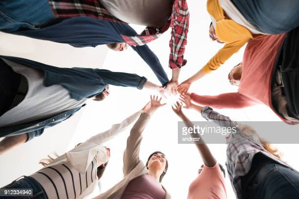 group of workers with hands together in a circle at a creative office - mani incrociate foto e immagini stock