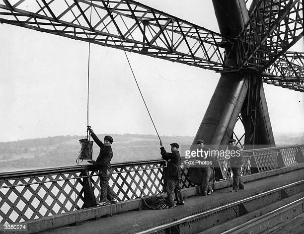 A group of workmen lowering supplies of paint in order to continue their task of painting the Forth Bridge which is over a mile long The steel...