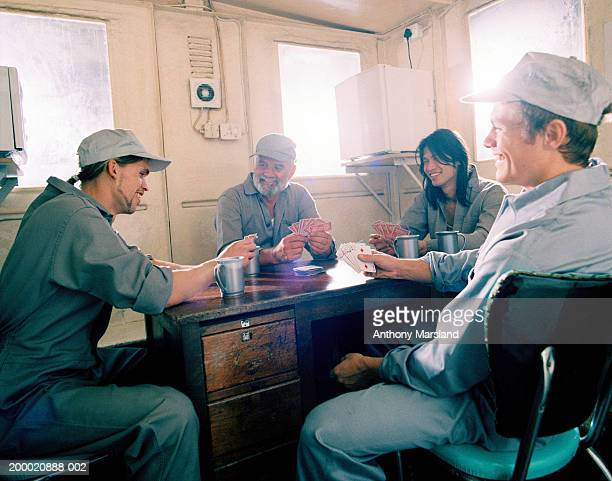 Group of workmen playing cards at table, smiling