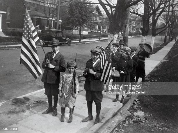 Group of y oung boys and girls parade on a sidewalk carrying flags and other patriotic items, Avondale, Ohio, 1918.