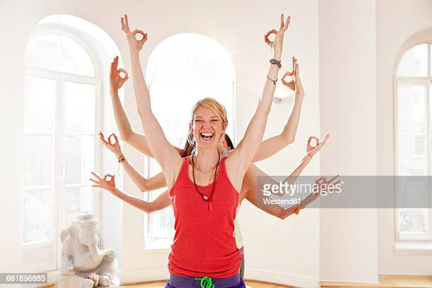Group of yoga people forming their arms like the hands of the many-armed goddess