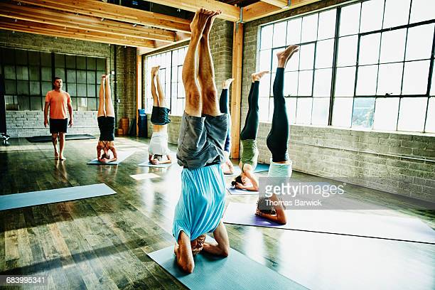 Group of yoga students in headstand pose