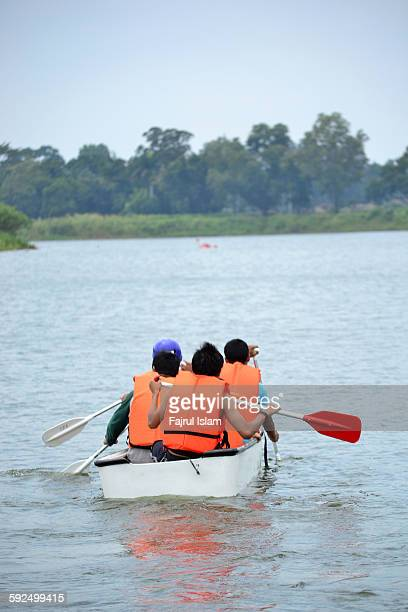 Group of young adult boating on river