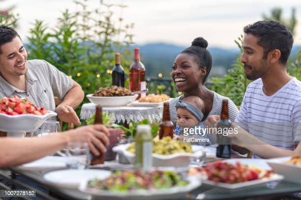 a group of young adult friends dining al fresco on a patio - nigeria stock pictures, royalty-free photos & images