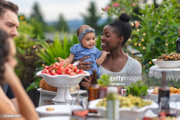 a group of young adult friends dining al fresco on a patio - african american family dinner stock photos and pictures