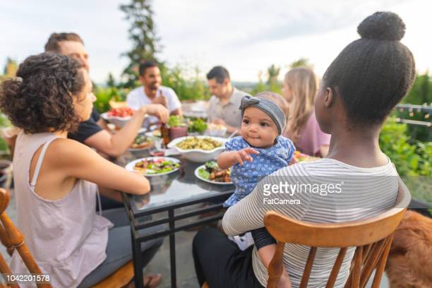 a group of young adult friends dining al fresco on a patio - nigerian food stock pictures, royalty-free photos & images