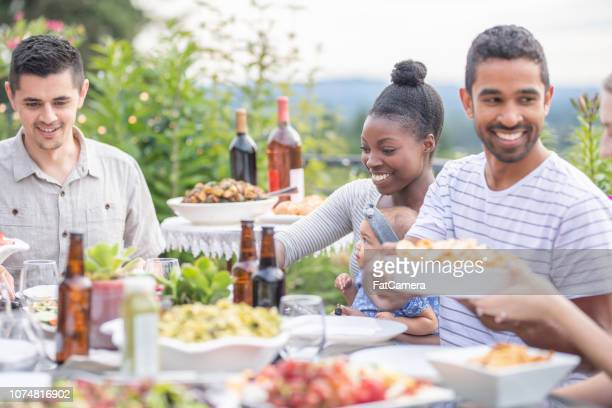 a group of young adult friends dining al fresco on a patio - filipino family dinner stock pictures, royalty-free photos & images