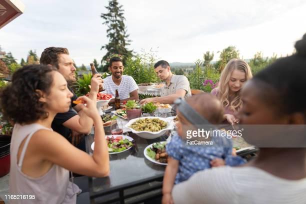 eine gruppe junger erwachsener freunde, die im freien auf einer terrasse essen - terrassenfeld stock-fotos und bilder