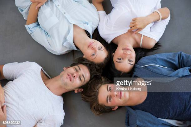 Group of young adult friends lying on a grey concrete floor studying/ working. Aerial view