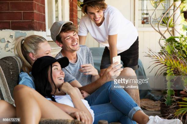 Group of young adults/ adolescent friends on the porch of an old house