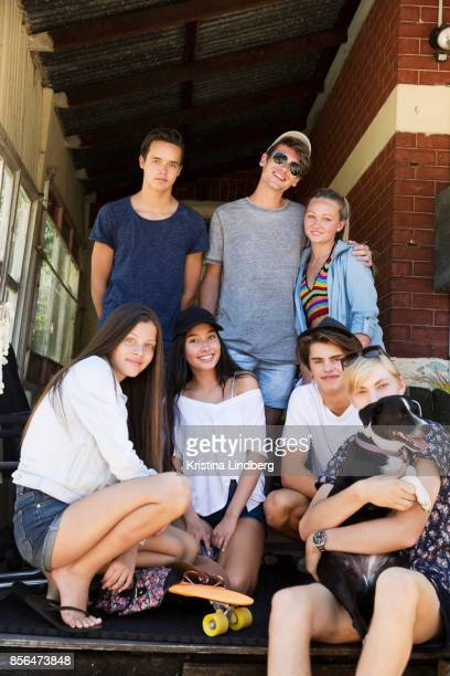 group of young adults/ adolescent friends on the porch of an old house - architectural feature stock pictures, royalty-free photos & images