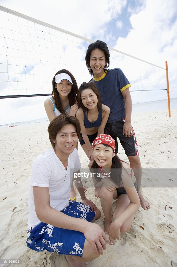Group of Young Adults by a Volleyball Net on the Beach : Stock Photo