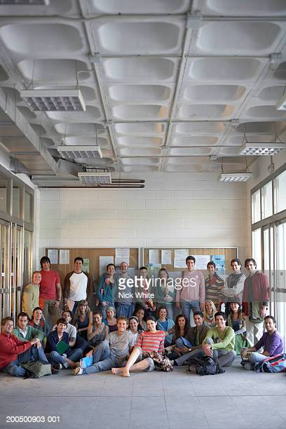 Group of young adults by notice boards, portrait
