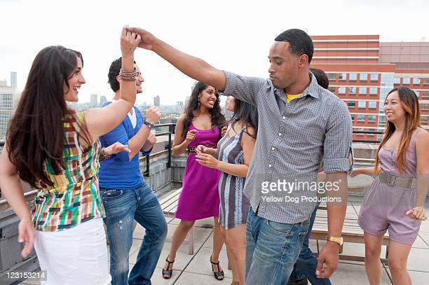 Group of Young Adults Dancing at Rooftop Party