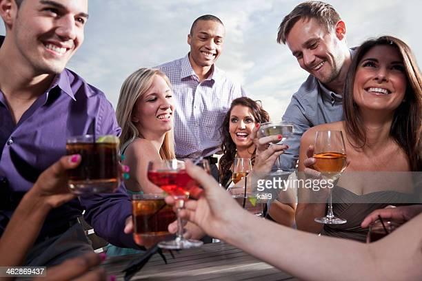Gruppe junger Erwachsener trinkt im Freien