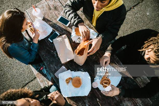 group of young adults eating fast food - take away food stock pictures, royalty-free photos & images