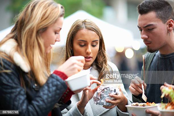 Group of young adults eating takeaway food, outdoors