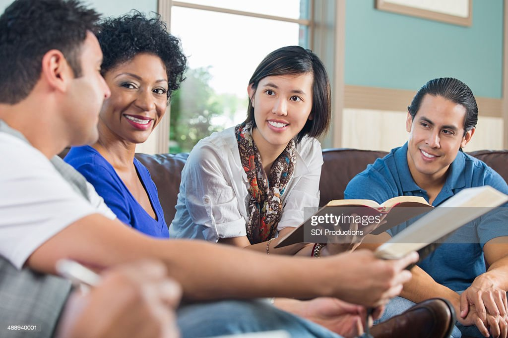 Group of young adults having discussion during bible study : Stock Photo