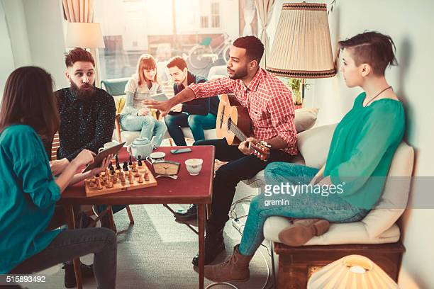 group of young adults having fun in coffee shop - game board stock photos and pictures
