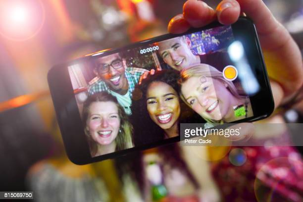 Group of young adults in bar taking photo of themselves