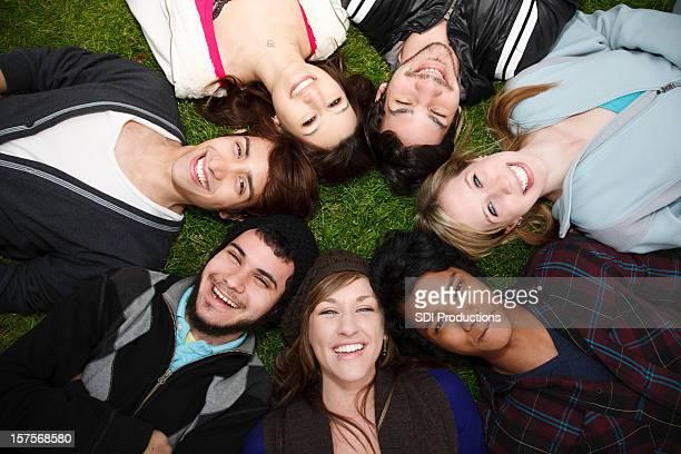 Groupe de jeunes adultes en cercle sur l'herbe