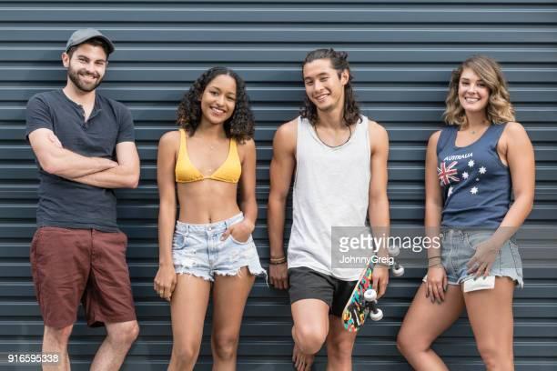 Gruppe junger Erwachsener in Sommerkleidung vor Wellpappe Hintergrund