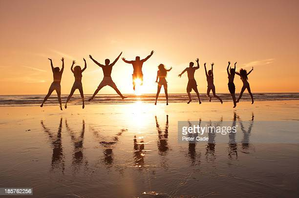 Group of young adults jumping on beach at sunset