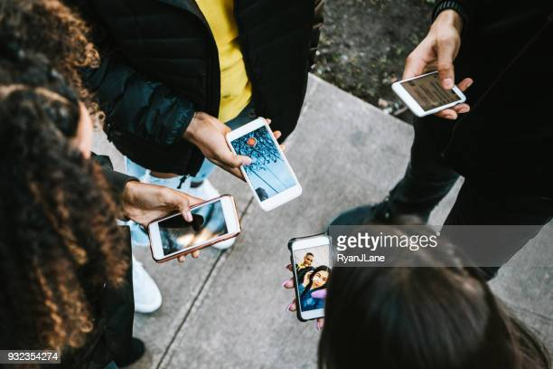 group of young adults looking at phone - social network foto e immagini stock