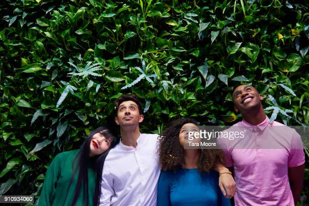 group of young adults looking up - four people stock-fotos und bilder