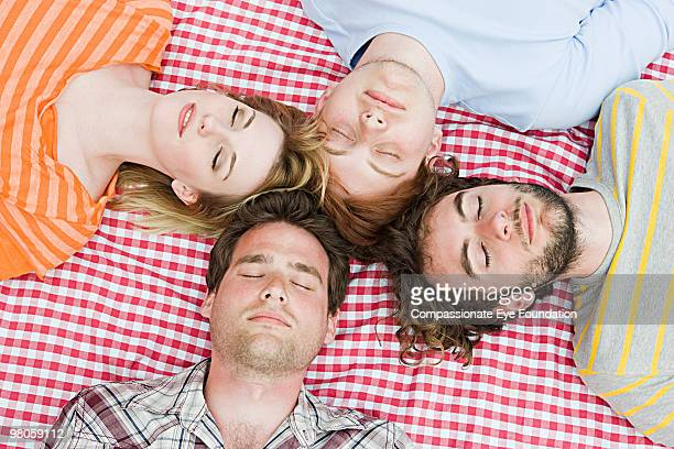 A group of young adults lying with eyes closed