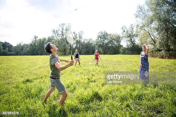 group of young adults playing badminton in field - badminton stock photos and pictures
