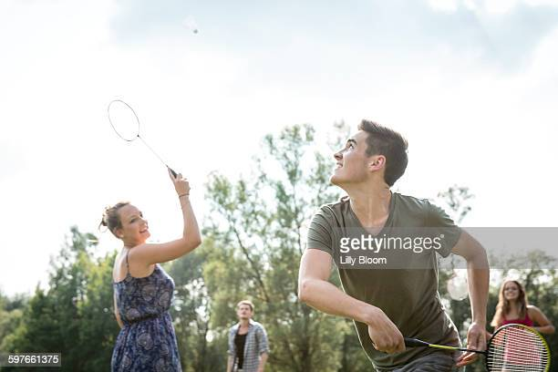 group of young adults playing badminton in field - badminton sport stock photos and pictures