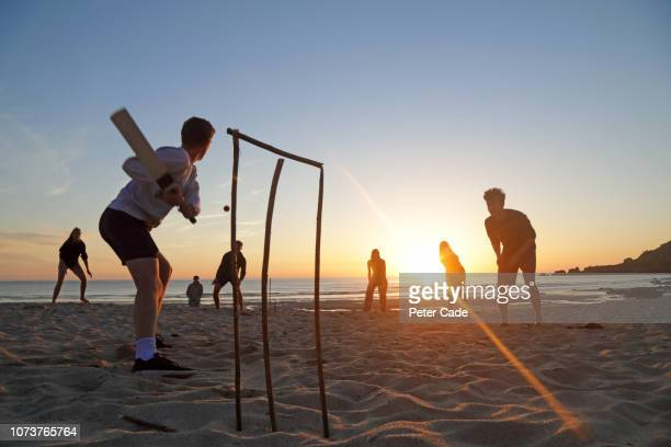 group of young adults playing cricket on beach at sunset - women cricket stock pictures, royalty-free photos & images