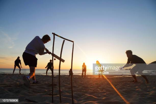 group of young adults playing cricket on beach at sunset - england cricket stock pictures, royalty-free photos & images