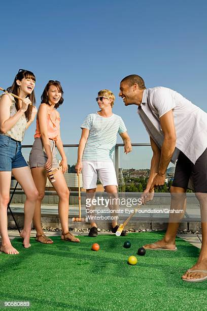 group of young adults playing croquet and laughing