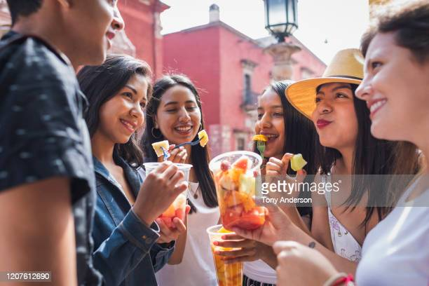 group of young adults sharing fruit - mexican picnic stock pictures, royalty-free photos & images