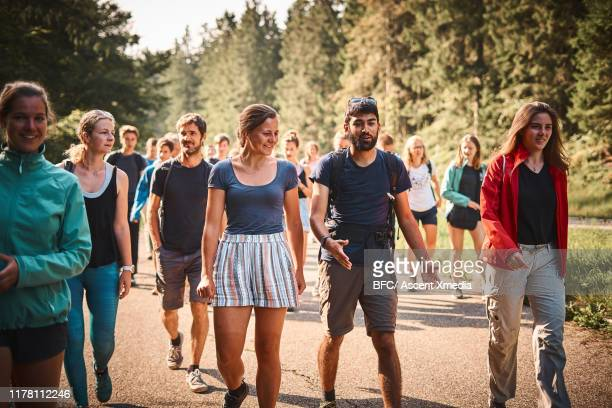 group of young adults walk along road in the forest - large group of people foto e immagini stock